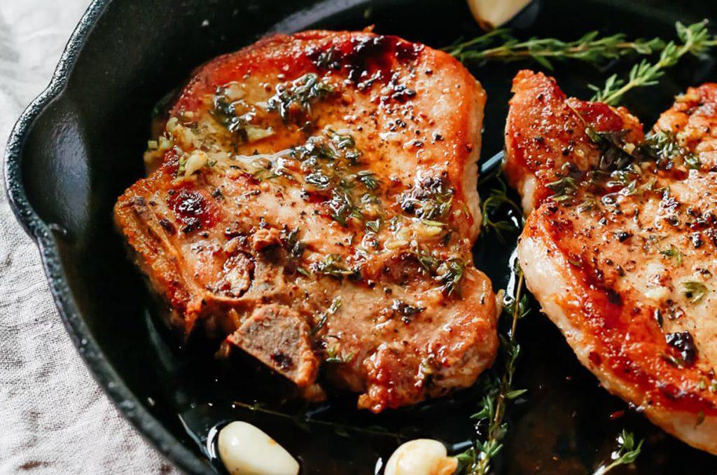 Стейк из свинины с розмарином, тимьяном и базиликом на сковороде