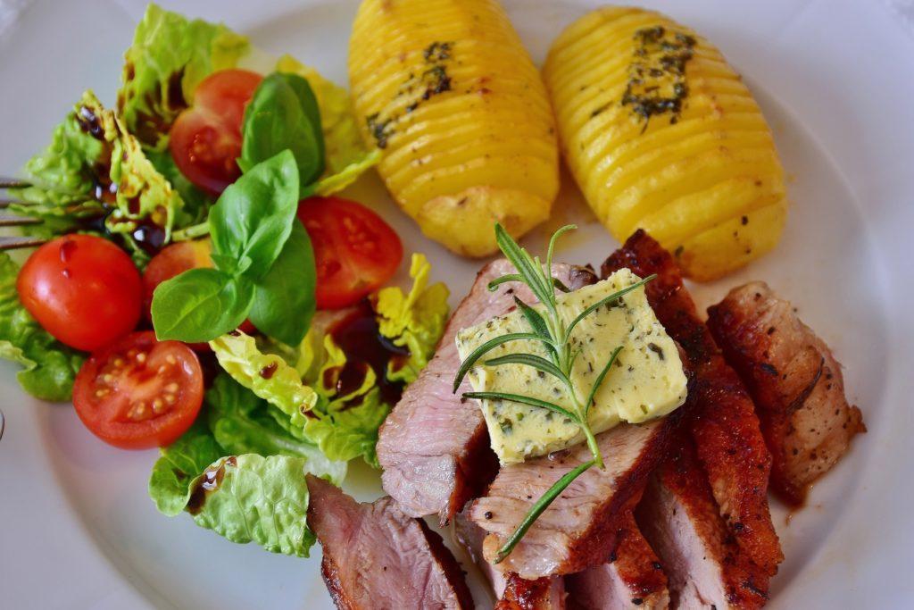 свиной стейк порезанный с салатом и картофелем