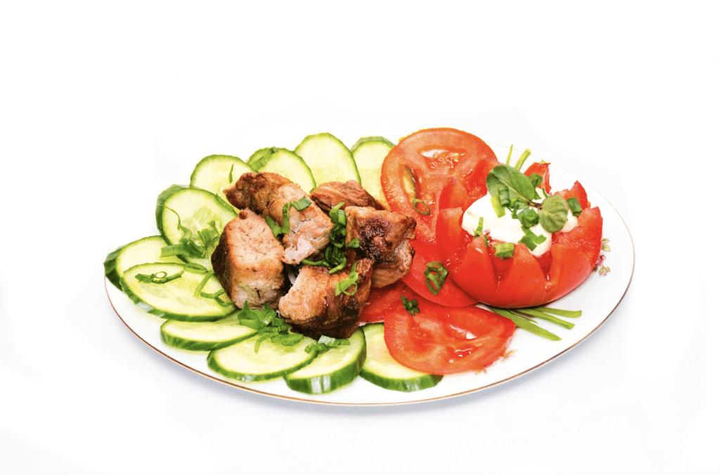 шашлык из свинины с овощами на тарелке